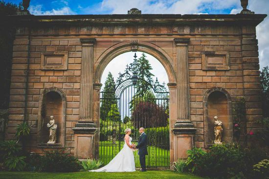 Newly wed couple in front of the gates at Chillington Hall